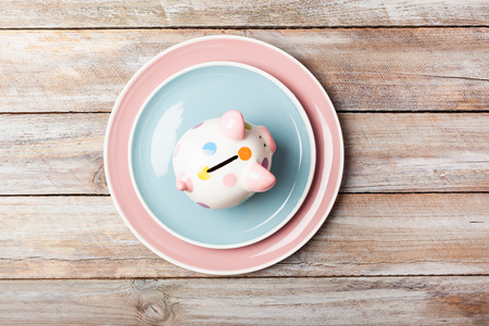 Empty  pastel colored plates and salad bowl with piggy bank for saving on cheap meal on grunge wood plank desk with copy space