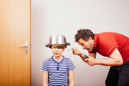 Stay at home situation: Father  cutting hair of son at home with pot and scissors during 2020 Covid-19 pandemic crisis