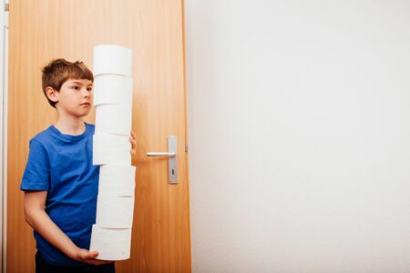 Boy bringing pile of toilet paper into room, hoarder family symbol image for covid-19 corona virus pandemic outbreak