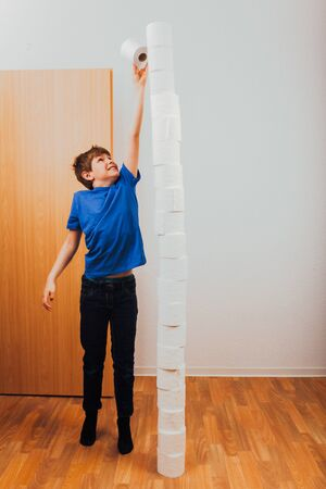 Boy balancing rolls of toilet paper in high stack as challenge during Covid-19 corona virus pandemic outbreak in 2020 Фото со стока