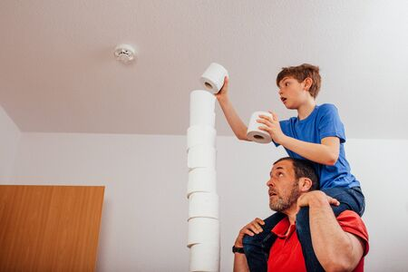 Father and son balancing rolls of toilet paper in high stack as challenge during Covid-19 corona virus pandemic outbreak in 2020