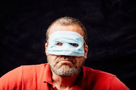 Adult man wearing face mask superhero style over eyes instead mouth and nose, studio portrait over black background