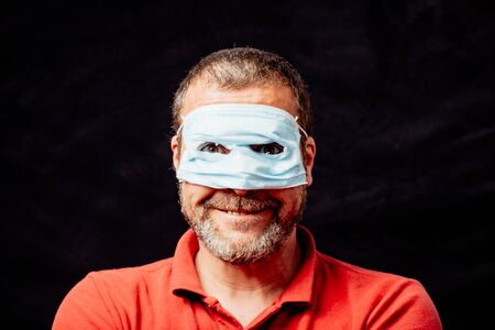Dumb man wearing face mask superhero style over eyes instead mouth and nose, studio portrait over black background Stockfoto