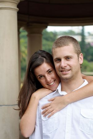 young happy caucasian couple hugging in the garden photo