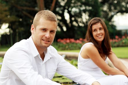 young happy couple sitting in the garden photo