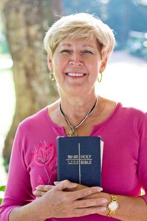 happy senior woman holding a bible photo