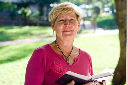 happy senior woman reading a bible Stock Photo