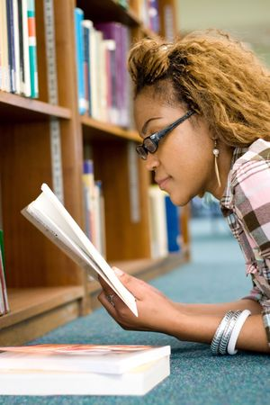 young female african student reading in library Stock Photo - 3922990
