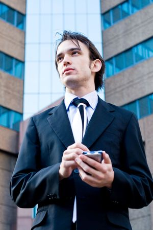 young handsome businessman (corporate executive) is using his palmtop (PDA) Stock Photo - 3931765