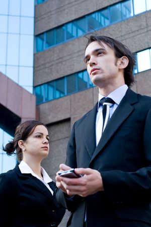 palmtop: well dressed business man standing next to a young beautiful business woman using a palmtop (PDA)