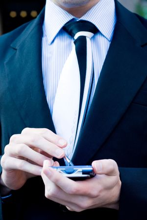 palmtop: young handsome businessman (corporate executive) is using his palmtop (PDA)