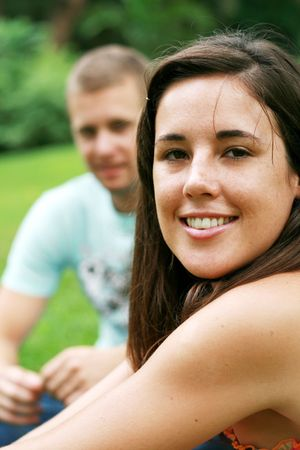 young couple sitting on grass and relaxing photo