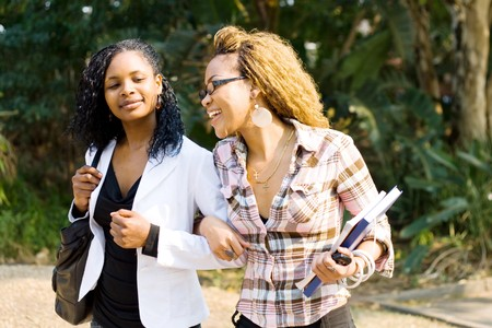 two african female college students walking to school classroom photo
