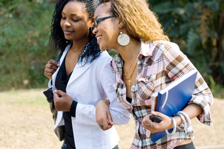 african education: two african female college students walking to school classroom