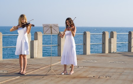 two beautiful women play violin on beach Stock Photo - 3944211