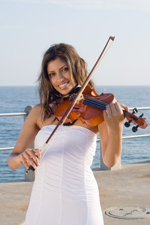 young indian woman play violin on beach photo