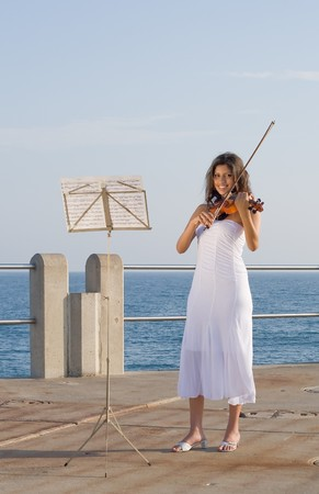 young indian woman play violin on beach Stock Photo