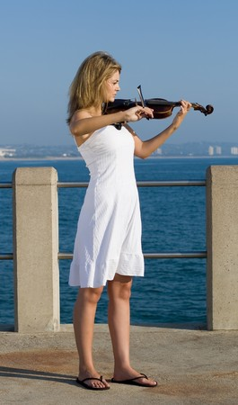 young beautiful blond woman play violin on beach pier