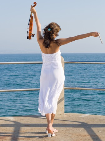 young woman holding posing arms up open with violin photo