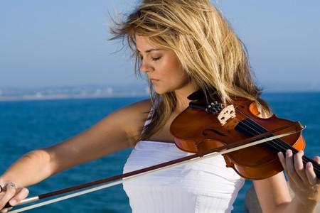 violist: mooie jonge blonde vrouw viool spelen op het strand