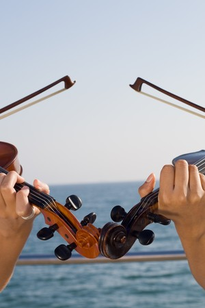 two beautiful young women play violins on beach photo