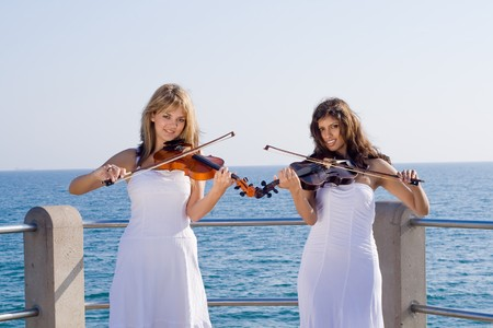 two beautiful young women with violins on beach photo