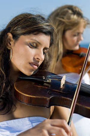 two beautiful young women play violin on beach photo