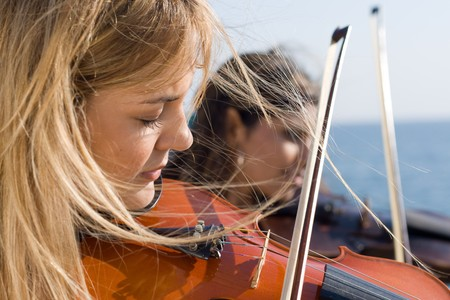 two young beautiful woman play violin on beach photo