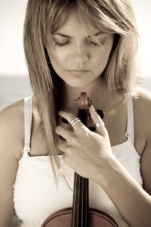 woman violin: young pretty thoughtful blond woman with violin on beach