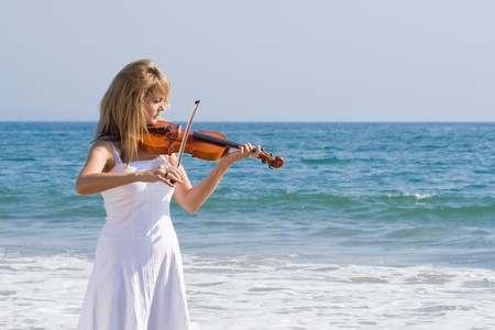 woman violin: young beautiful female blond woman play violin on beach Stock Photo
