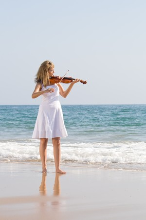 young beautiful female blond woman play violin on beach Stock Photo