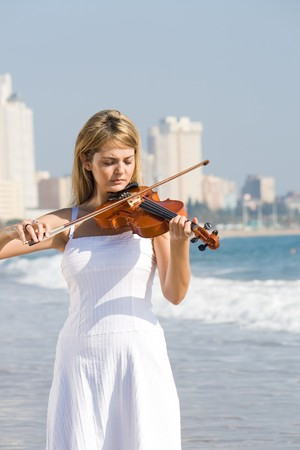 young beautiful female blond woman play violin on beach photo