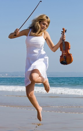 young beautiful blond woman jump on beach with a violin photo