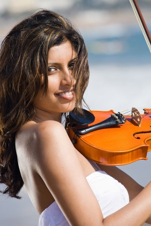 indian ocean: beautiful young indian woman play violin on beach
