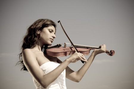 girl in dress: beautiful young indian woman play violin on beach