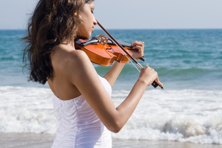 young beautiful indian woman play a violin walking on beach
