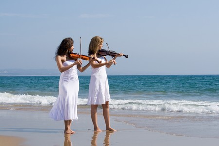 two young beautiful vionists play violins on beach Stock Photo