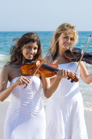 two young beautiful vionists play violins on beach photo