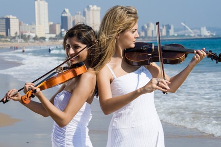 two young beautiful female violinist play violin on beach photo