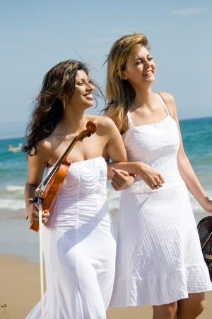 two young female violinists walking on beach photo