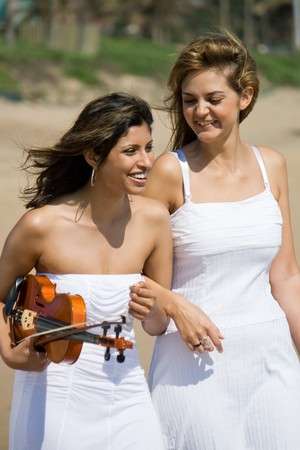two happy young women friends with violin walking on beach photo