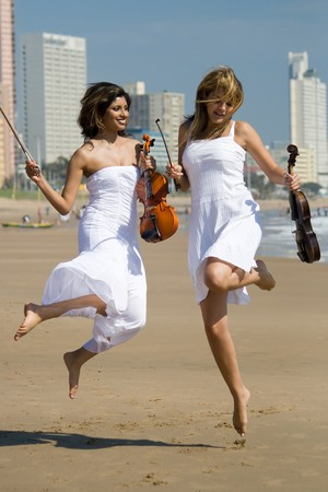 two young women jump on beach with violins photo