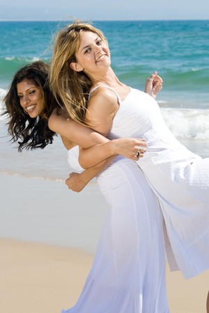 two happy young women best friends on beach photo