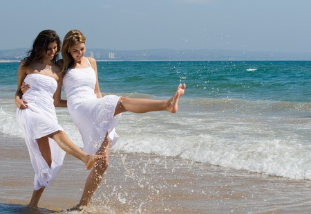 young female: two happy young women best friends on beach