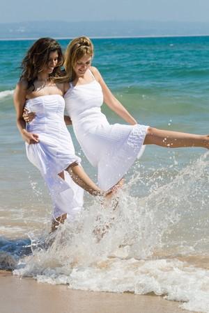 two women friends having fun on beach photo