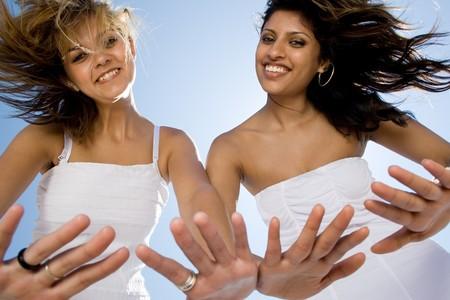 indian ocean: two young women friends having fun on beach