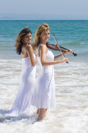 two young woman play violins on beach in sea water