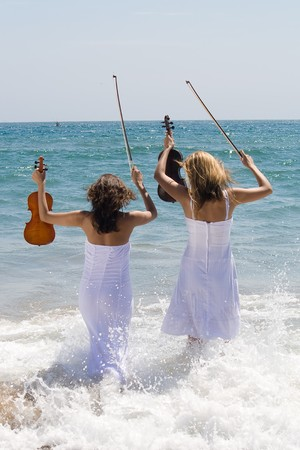 two woman with violin on beach having fun photo