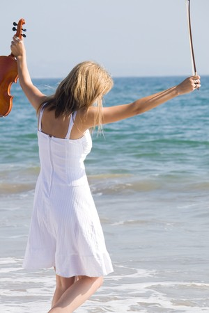 young beautiful female violinist play on beach photo