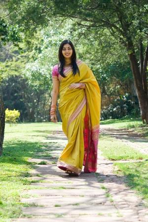 sari: India hermosa mujer caminando en el jard�n Foto de archivo